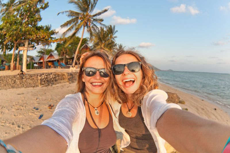 Two happy girlfriends making selfie on the coast of tropical sea
