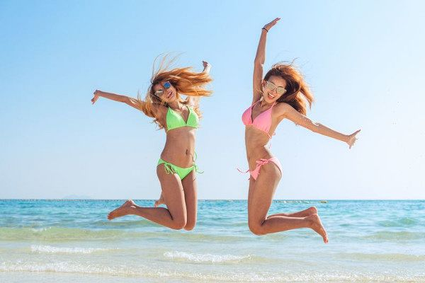 Happy bikini two asian women jumping of joy and success on perfect white sand beach on italian vacation. Holiday girls with sexy slim suntan body running of freedom and happiness.