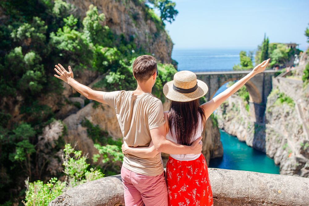 Happy couple enjoy the amazing view of Fiordo di Furore. Cala di Furore beach, bridge over the gorge Fiordo di Furore.