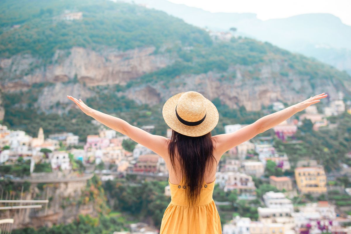Back view of young woman in straw hat and yellow dress with Positano village on the background, Amalfi Coast, Italy