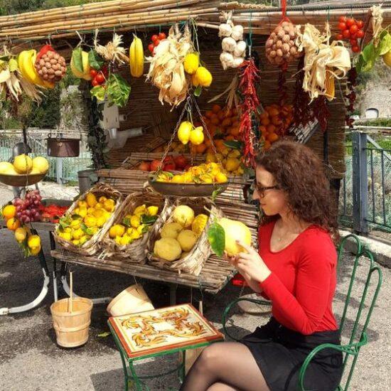 Girl sitting next to fruit cart. Watching the lemos from Amalfi Coast.
