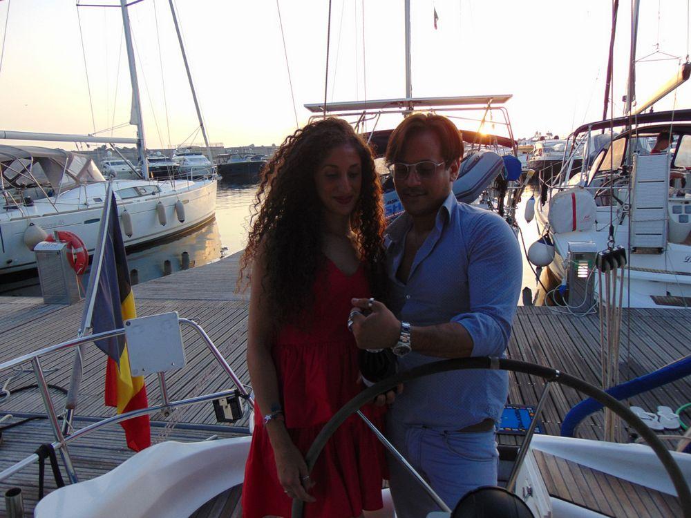Coppia in barca stappa una bottiglia per festeggiare il loro anniversario