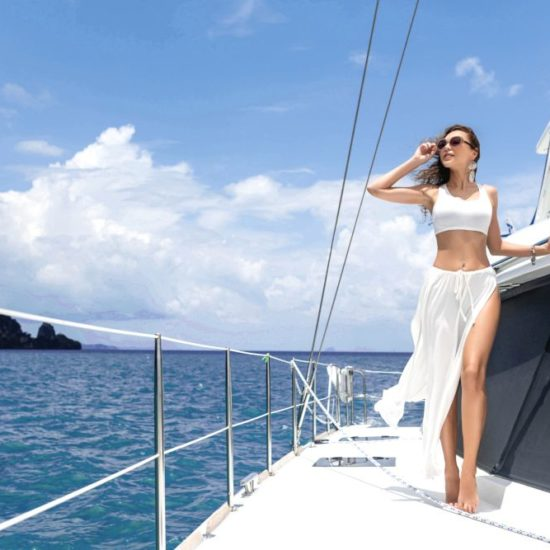 Young beautiful girl with long hair standing on the bow of the yacht in white skirt and bikini.