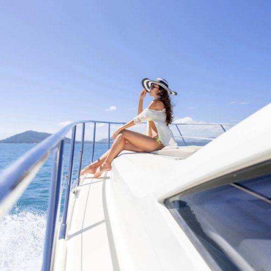 Fashion photo of adorable young woman sitting on edge of luxury yacht and looking for the sea during sailing trip. Happy woman enjoying summer travel. Vacation concept