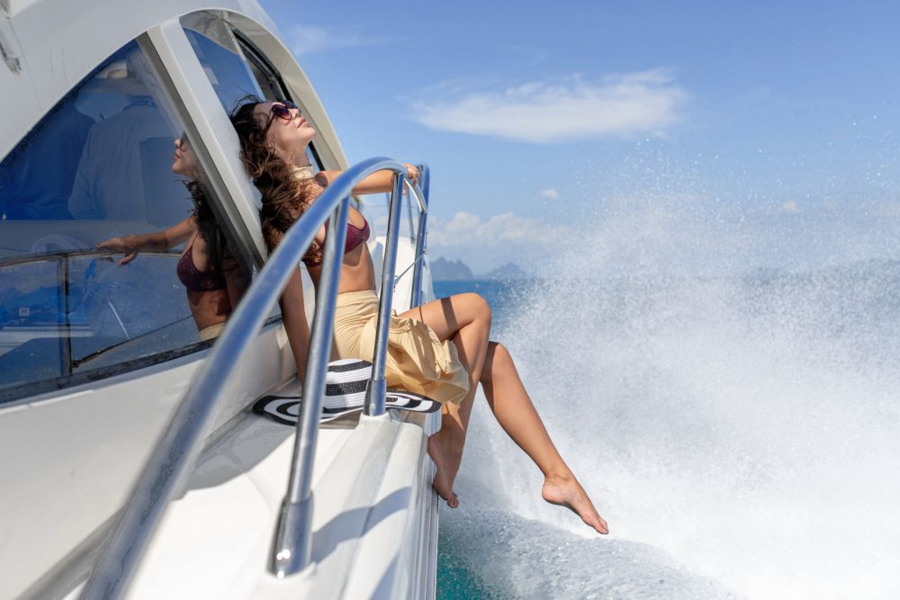 Young beautiful girl with long hair sitting on the bow of the yacht in white skirt and bikini.