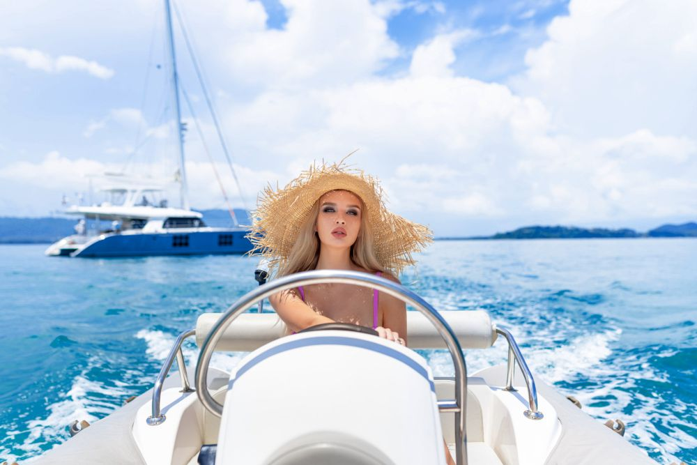 Young girl with bright makeup in a pink bikini posing sitting while driving a small motor boat. Close-up. Travel. Marine beauty. The waves. On the background of the yacht.