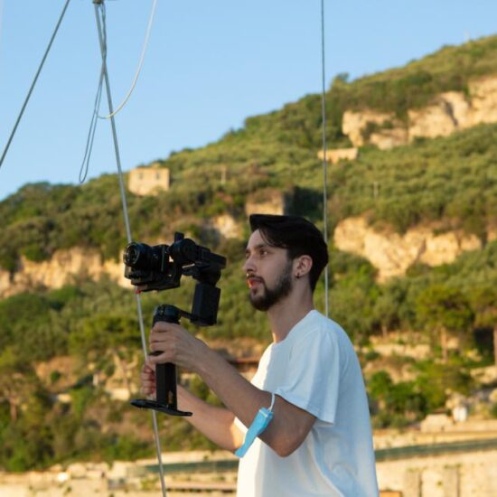 Vacation Photographer taking a couple in video. Boat in Sorrento Coast with beautiful sunset