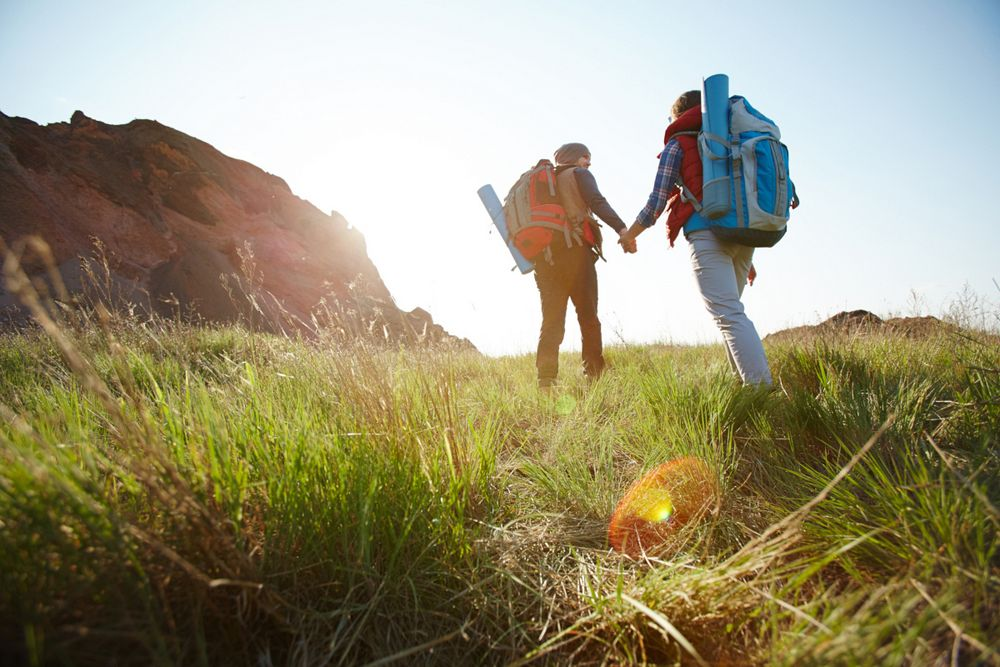 Romantic adventure of young tourist couple, low angle of man and woman going uphill holding hands towards bright sunlight on hiking path in mountains