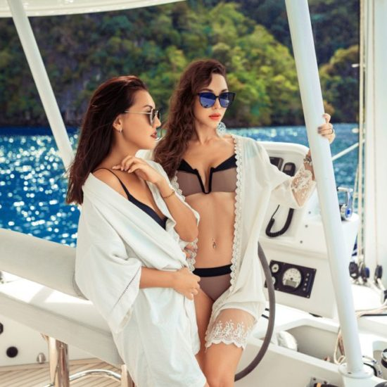 Two girls run the yacht . Summer cruise on the yacht. Friends traveling by yacht on the sea. Holiday on a yacht. Back view