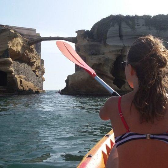 Ragazza in kayak rema nella zona della Gaiola, Posillipo.
