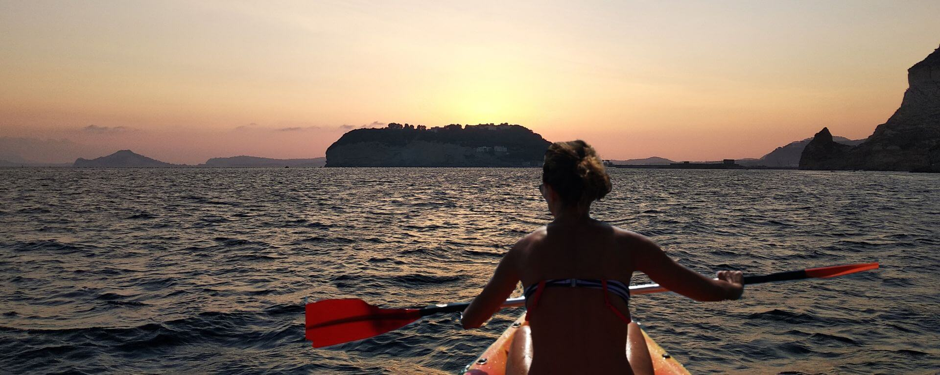 Ragazza in kayak che rema verso il tramonto: Posillipo