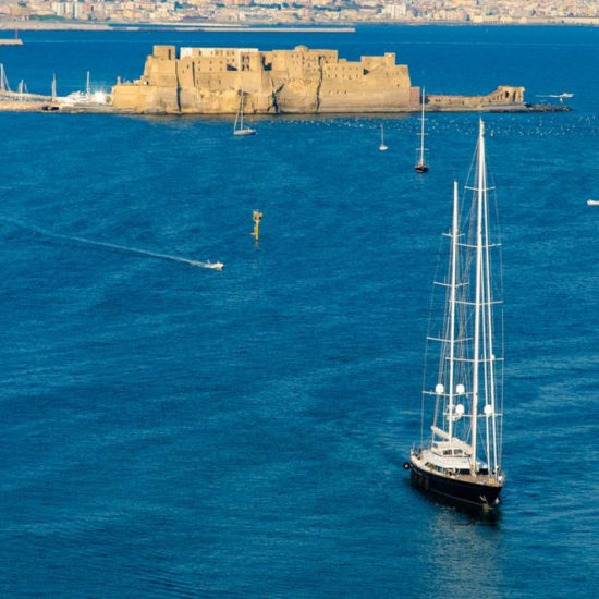 Sailboat at Tyrrhenian sea and Egg castle on background in Naples, Italy. Aerial view, card design.