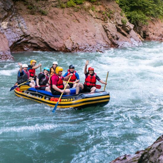 A group of men and women are rafting on the river, extreme and fun sport. RUSSIA, GUZIRIPL. August, 2019