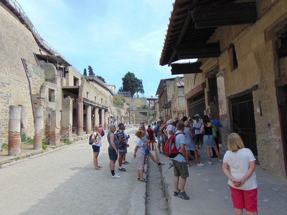 people standing in front on a old shop of Ercolano ruins