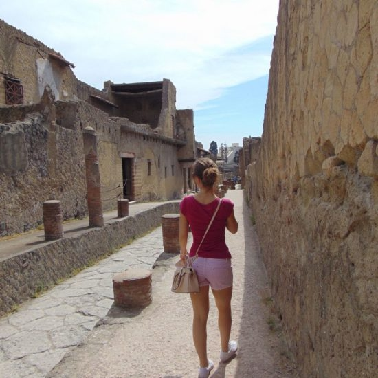 Girl walking in the street of ancient Ercolano