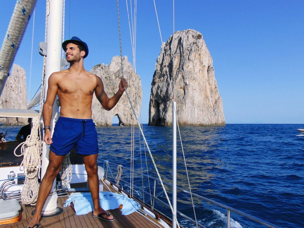 Young beautiful man standing in swimming suit on a yacht near blue sea water of Capri