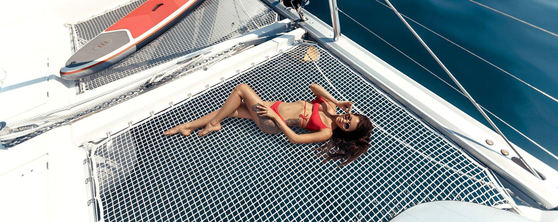 Bellissima ragazza è distesa nella rete del catamarano, prendendo il sole a Capri