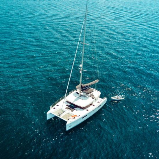 Aerial drone top view photo of luxury yacht with white rubber boat. Capri island.