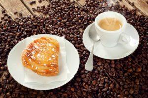 Neapolitan Sfogliatella riccia with cup of espresso coffee