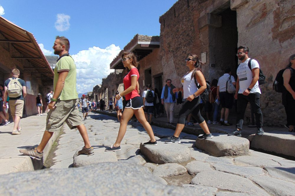Four young people walk in pompeii like the Beatles in Abbey Road