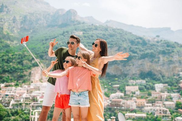 Family vacation in Europe. Family of four taking selfie photo background Positano on Amalfi coast