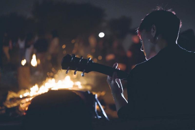 ragazza suona la chitarra davanti a persone che siedono intorno al fuoco